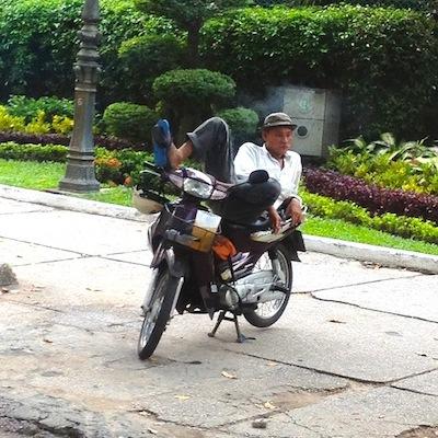 バイクの上に寝るおじさん